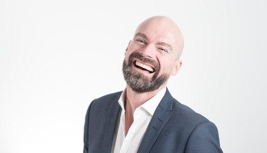 アイロンがかけてある白シャツを着て笑う男性