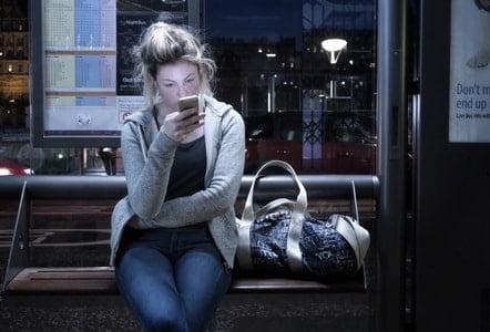 ワクワクメールの伝言板を無表情で眺める女性
